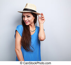 Smiling beautiful young woman with straw hat on blue background with empty copy space