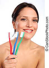 Smiling beautiful young woman with toothbrushes