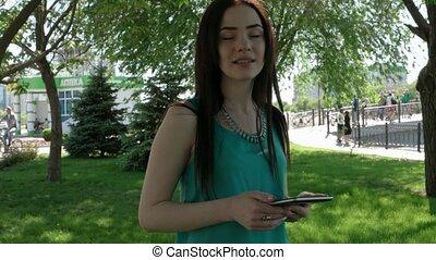 Smiling beautiful young women speaking outdoors