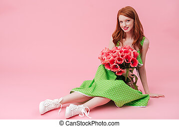 Smiling beauty woman sitting on floor with bouquet of flowers