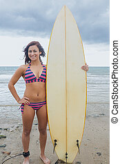 Smiling bikini woman holding surfboard at beach