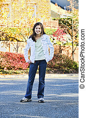 Smiling biracial eleven year old girl standing in middle of street
