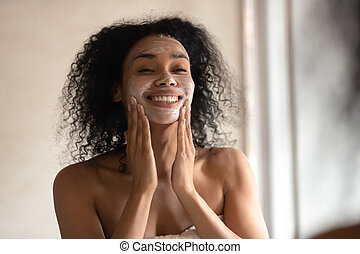 Smiling biracial woman apply face mask after shower - Close ...