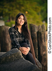Smiling biracial young woman sitting on rocks outdoors at sunset