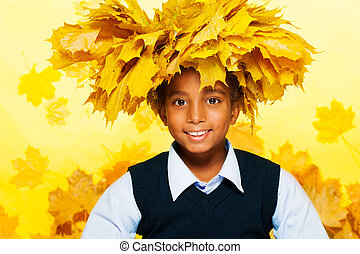 Smiling black boy wearing maple leaves crown