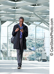 smiling black businessman walking with cell phone at airport