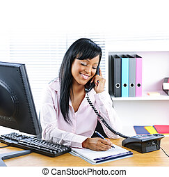 Smiling black businesswoman on phone at desk - Smiling young...