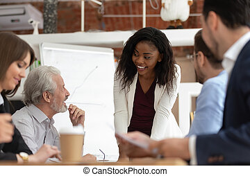 Smiling black businesswoman talk with colleagues heading meeting