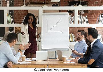 Smiling black female coach make flip chart presentation