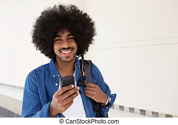 Smiling black man walking with cell phone