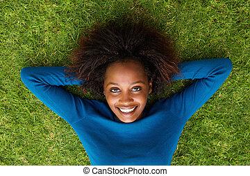 Smiling black woman lying on grass