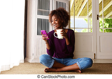 Smiling black woman sitting on floor at home with cell phone