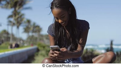 Smiling black woman texting with smartphone
