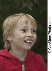 Smiling blond boy looks to the right.