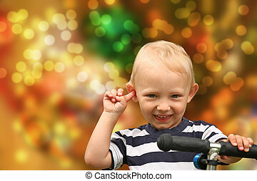 Smiling blond boy with his finger in the ear