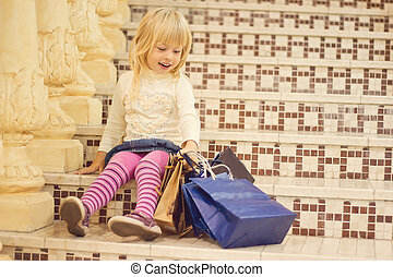 Smiling blond girl 3 years old with shopping