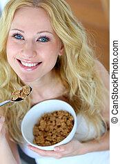 Smiling blond girl eating cereals for breakfast