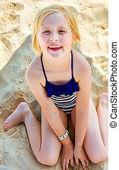 smiling blond girl sitting in swimwear on beach