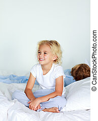 Smiling blond girl sitting on a bed