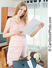 Smiling blond pregnant woman with documents in home interior