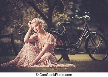 Smiling blond retro woman in summer dress sitting on a meadow