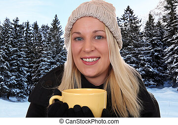 Smiling blond woman drinking cup of tea outdoor in winter