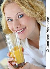 Smiling blond woman drinking orange juice
