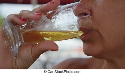 Smiling blond woman drinking shimmering beer on a sea shore in slow motion