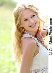 Smiling blond woman in meadow during summer