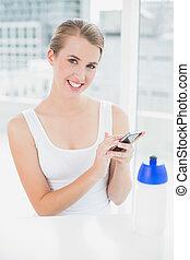 Smiling blond woman sending a text message