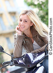 Smiling blond woman sitting on motorbike
