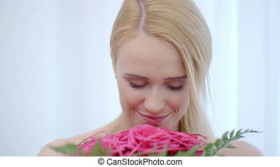 Smiling Blond Woman Smelling Pink Roses - Close up Smiling...