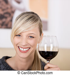 Smiling blond woman toasting with a glass of wine