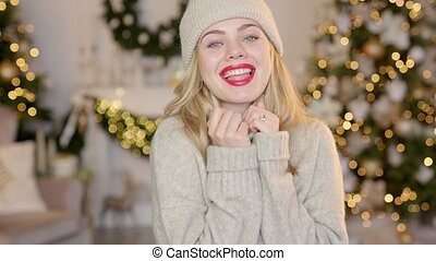Smiling blond woman with red lipstick, dressed in a warm woolen cardigan and hat posing in her home