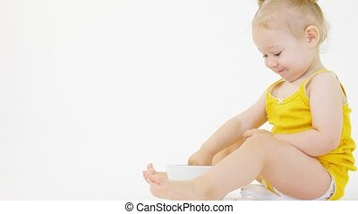 Smiling blonde baby girl eating her meal against white background