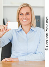 Smiling blonde businesswoman holding a card looks itno camera