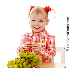 Smiling blonde child eat at the table
