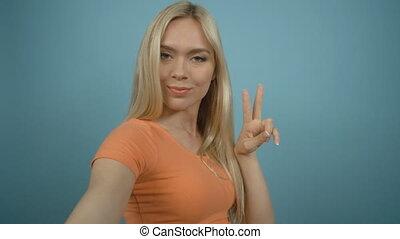 Smiling blonde girl in orange T-shirt taking selfie with...