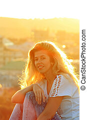 smiling blonde girl in the sunlight, cityscape background