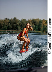 Smiling blonde girl riding on the red wakeboard on the lake