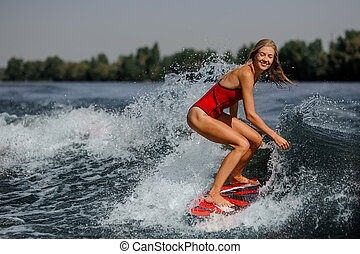 Smiling blonde girl riding on the red wakeboard