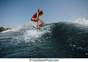 Smiling blonde girl standing on the red wakeboard on the lake