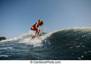 Smiling blonde girl standing on the wakeboard on the lake