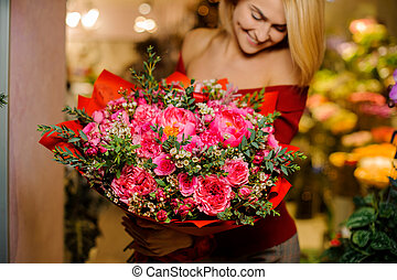 Smiling blonde girl with a large and bright bouquet of flowers for the Valentine s day