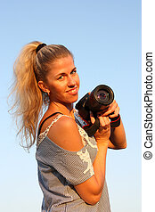 Smiling blonde girl with camera in hand.
