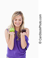Smiling blonde holding an apple and a muffin