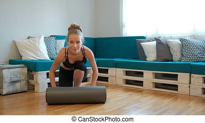 Smiling blonde in sports clothes exercising home sitting on floor indoors