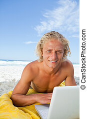 Smiling blonde man looking at the camera while using his laptop