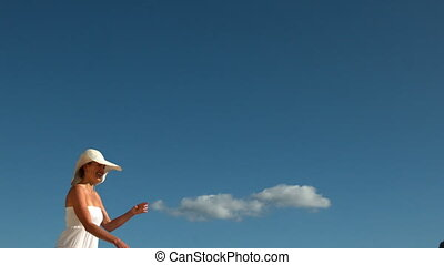 Smiling blonde running and taking off her sunhat in slow...
