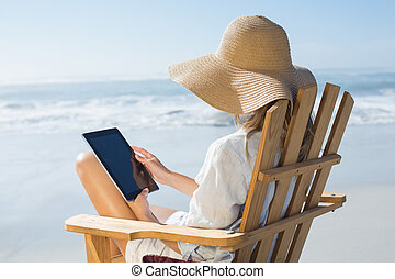 Smiling blonde sitting on wooden deck chair by the sea using...